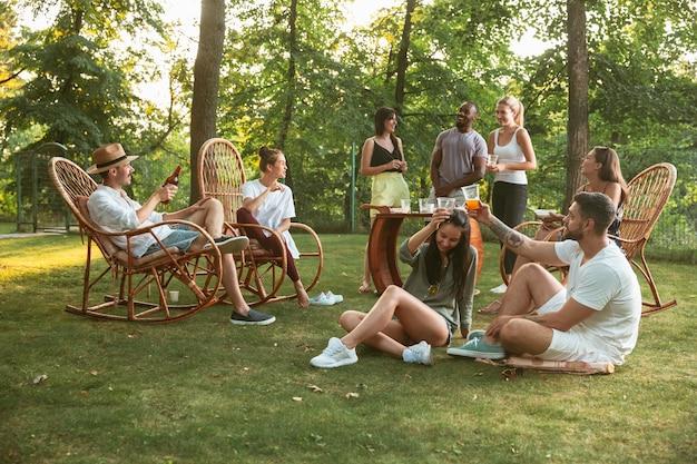 Amici felici che mangiano e bevono birre alla cena barbecue sull'ora del tramonto