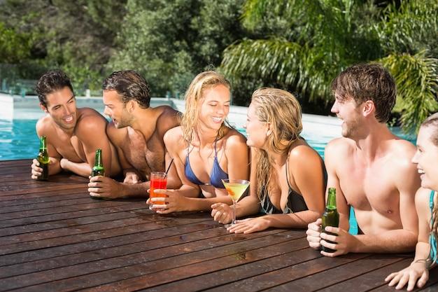 スイミングプールで楽しんで幸せな友達