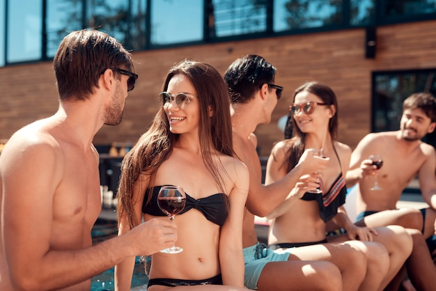Happy friends enoying pool party. summer vacation concept