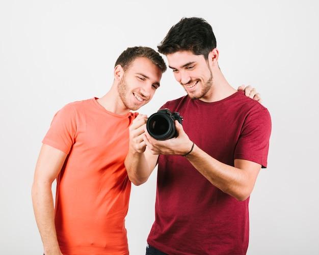 Happy friends exploring camera device