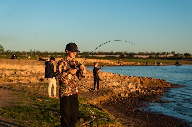 Счастливые друзья, ловящие рыбу на берегу реки.