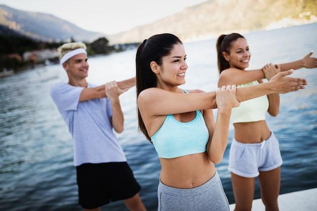 야외에서 활동적인 건강한 생활을 함께 하는 행복한 친구들의 피트니스 훈련