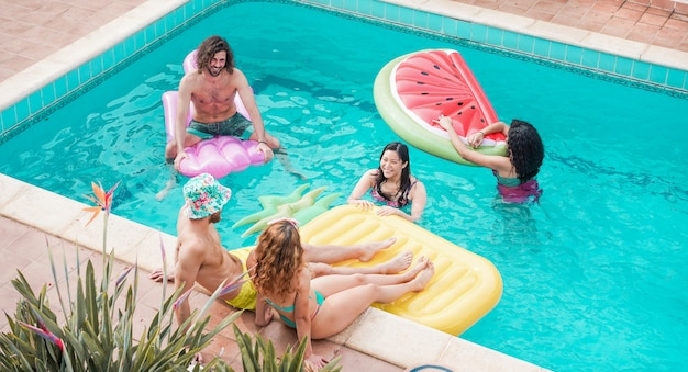 Happy friends floating with air lilo ball at swimming pool party - young people having fun on summer holidays vacation