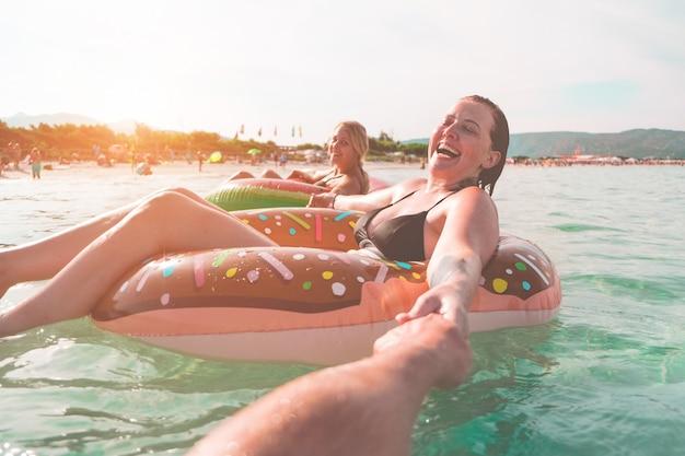 Счастливые друзья плавают с матрасом лилос в море