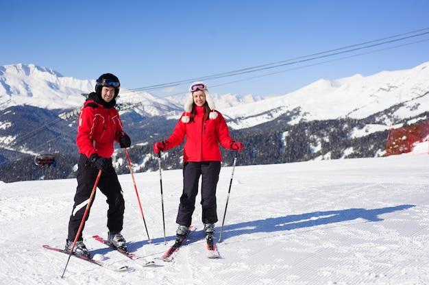 Счастливые друзья собираются кататься на лыжах в зимние каникулы - молодой coulpe развлекается, занимаясь экстремальным спортом - концепция дружбы и праздников