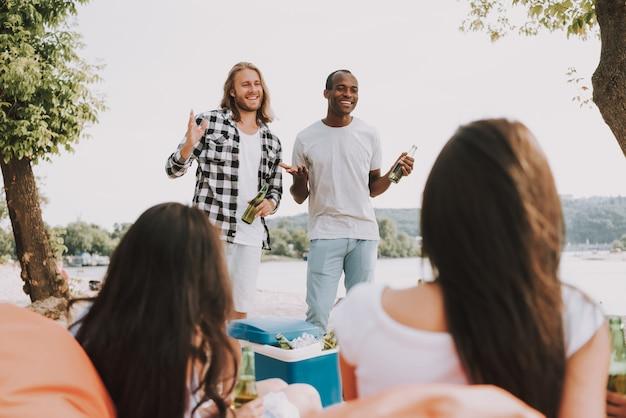 幸せな友達がビーチパーティーにビールを飲みました