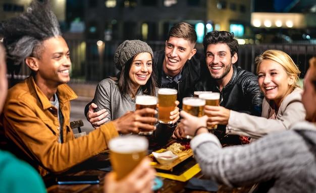 Группа счастливых друзей пьет пиво в пивном баре на открытом воздухе