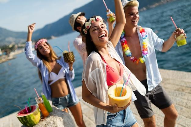 Группа счастливых друзей, весело проводящих время на пляжной вечеринке, пить коктейль на закате. концепция летней радости и дружбы с молодыми людьми в отпуске