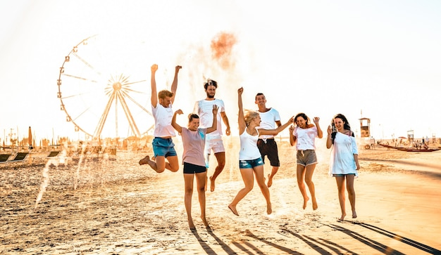 Happy friends group having fun at ferris wheel seaside
