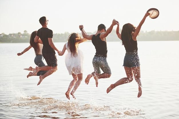 幸せな友達がビーチで楽しい時を過す-夏休みに戸外で遊ぶ若者。
