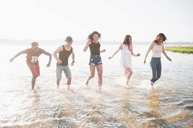 Счастливые друзья веселятся на пляже - молодые люди играют в воде под открытым небом во время летних каникул.