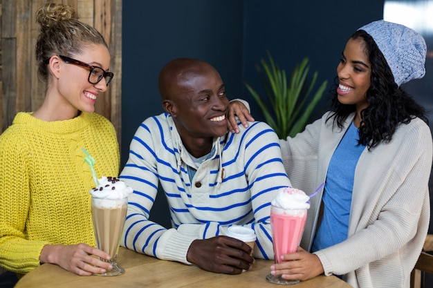 Счастливые друзья пьют кофе и молочные коктейли в кофе