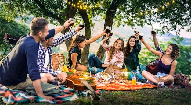 Счастливые друзья веселятся в винограднике на закате