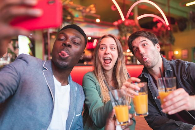 Happy friends having fun at bar and taking a selfie