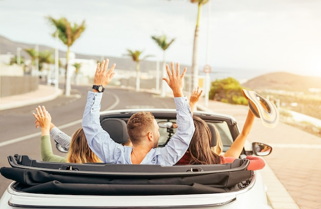 Happy friends having fun in convertible car at sunset in vacation