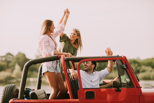 Happy friends having fun in convertible car at vacation