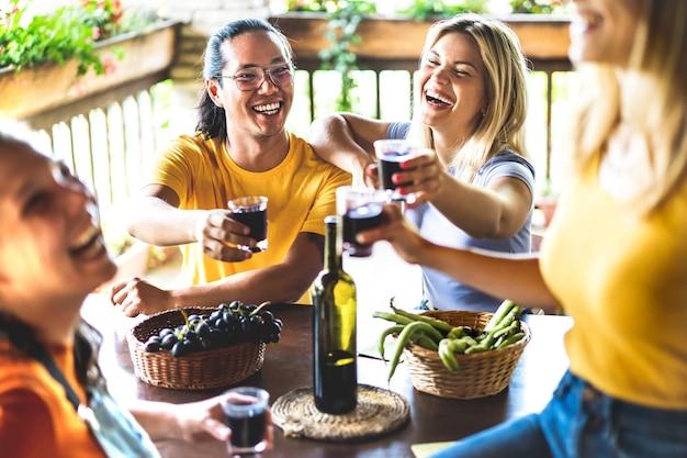 Счастливые друзья веселятся и пьют во внутреннем дворике с виноградником