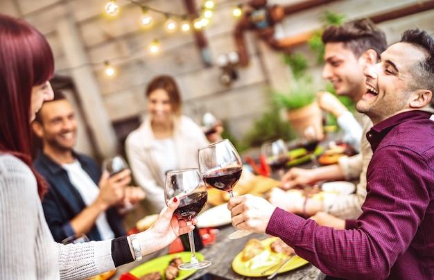 プライベートディナーパーティーでバルコニーで赤ワインを飲むのを楽しんでいる幸せな友達
