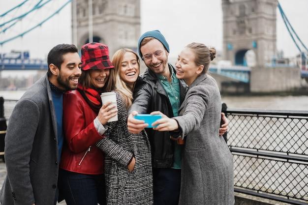 Счастливые друзья веселятся, принимая селфи-смартфон в лондоне на фоне тауэрского моста - сосредоточьтесь на лице девушки в центре
