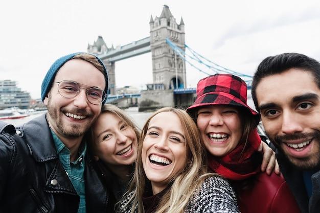 タワーブリッジを背景にロンドンで携帯電話で自分撮りを楽しんでいる幸せな友達-中央の女の子の顔に焦点を当てる