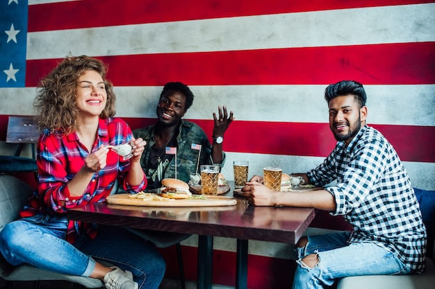 Amici felici che riposano insieme al bar, donne e uomini al bar, parlando, ridendo mangiano fast food.