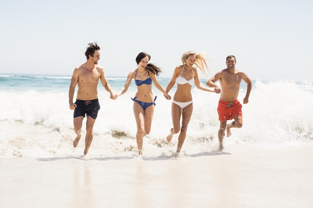 Happy friends holding hands and running on the beach