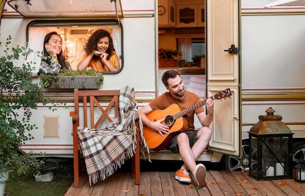 Счастливые друзья в фургоне играют на гитаре