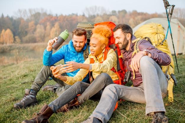 キャンプ場近くの緑の芝生に座ってスマートフォンを楽しんでいるバックパックとカラフルなジャケットで幸せな友達