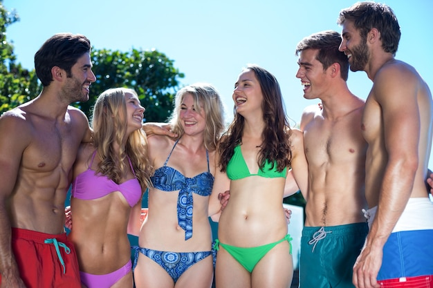 一緒に立っている水着の幸せな友達