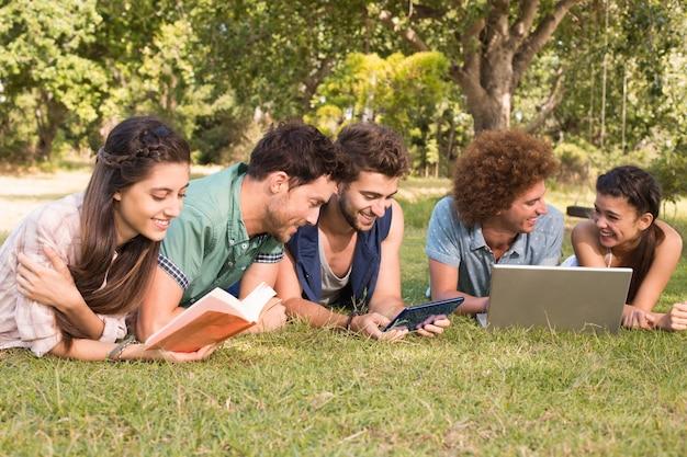 公園で幸せな友達が勉強している