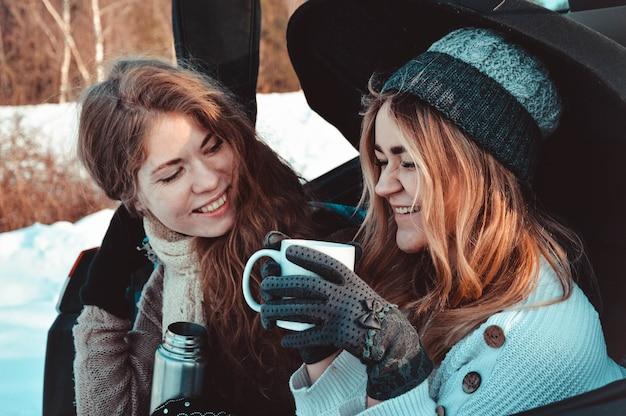 車の中で冬の森の幸せな友達。 2人の幸せな女の子が魔法瓶からコーヒーを飲みながら車のトランクに座って、話したり笑ったりします。