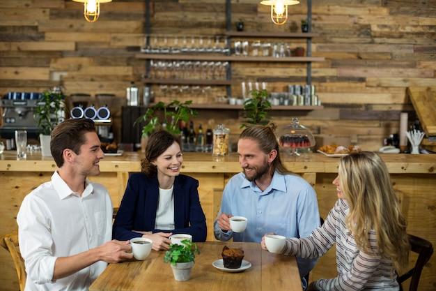 コーヒーを飲みながらお互いに相互作用する幸せな友達