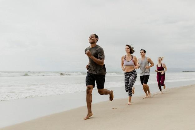 Счастливые друзья бегают вместе на пляже