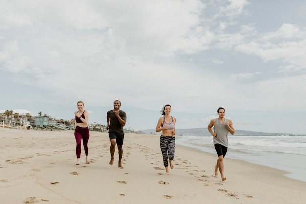 Happy friends jogging together at the beach