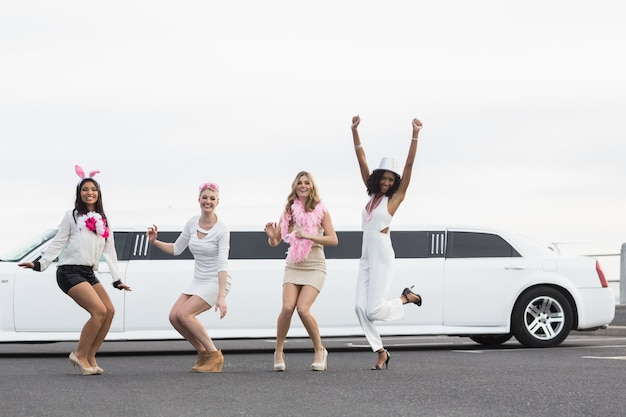 Happy friends jumping in front of a limousine
