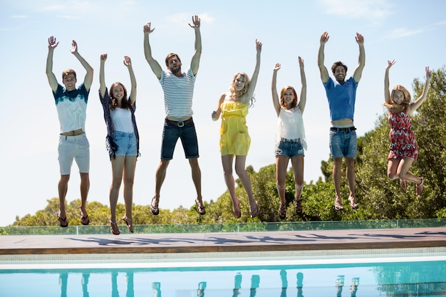 Happy friends jumping near swimming pool