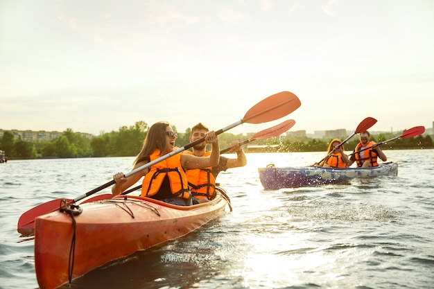Happy friends kayaking on river with sunset on the background