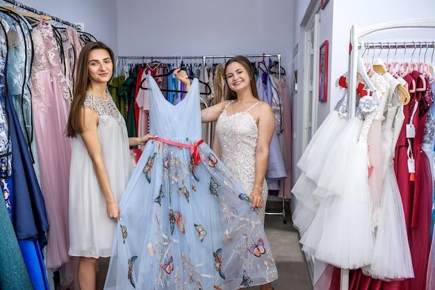 Счастливые друзья, глядя на платье в магазине одежды