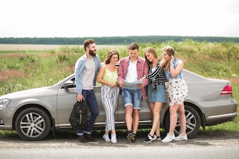 Happy friends looking at map standing near the car