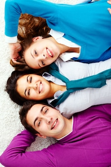 Happy friends lying down on a white carpet