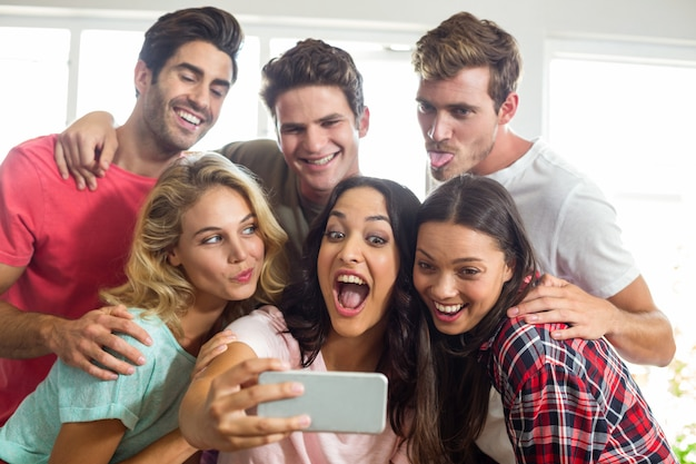 Happy friends making faces while taking selfie at home