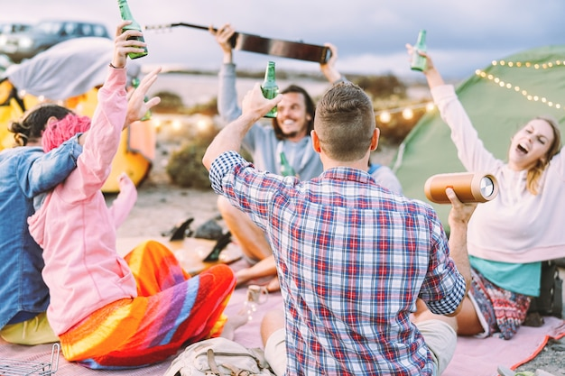 Happy friends making party drinking beers and playing music while camping with tents outdoor