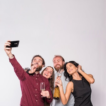Happy friends making selfie with champagne