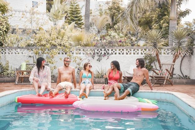 Счастливые друзья устраивают вечеринку у бассейна - молодые люди веселятся на летних каникулах