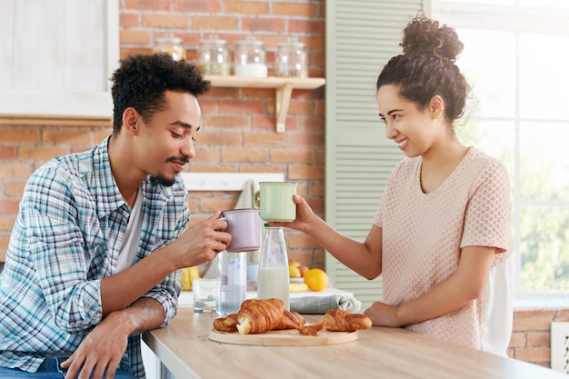 Happy friends meet together at home atmosphere, clink mugs, eat delicious croissants,