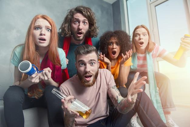 テレビでサッカーを見て勝利を祝うサッカーファンの幸せな友達