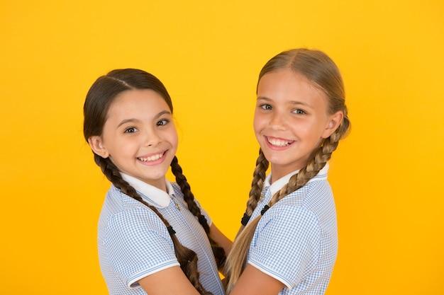 노란색 배경에 행복 친구입니다. 패션 뷰티. 어린 시절의 행복. 자매결연 개념. 복고 교복을 입은 작은 소녀들. 빈티지 스타일의 아이들. 올드 스쿨 패션. 우리는 함께입니다.