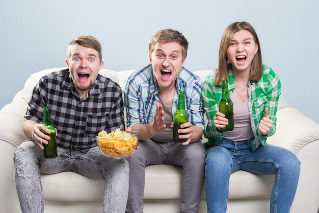 Счастливые друзья или футбольные фанаты смотрят футбол по телевизору и празднуют победу.