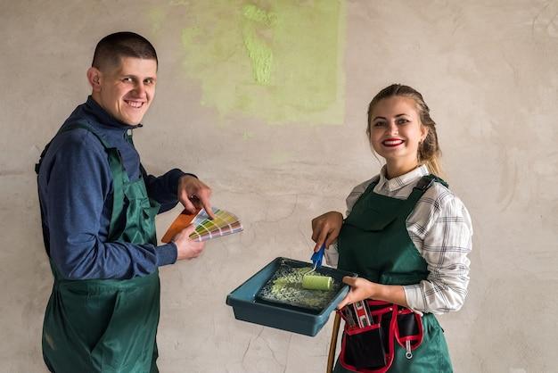 緑の色で壁を塗る幸せな友達