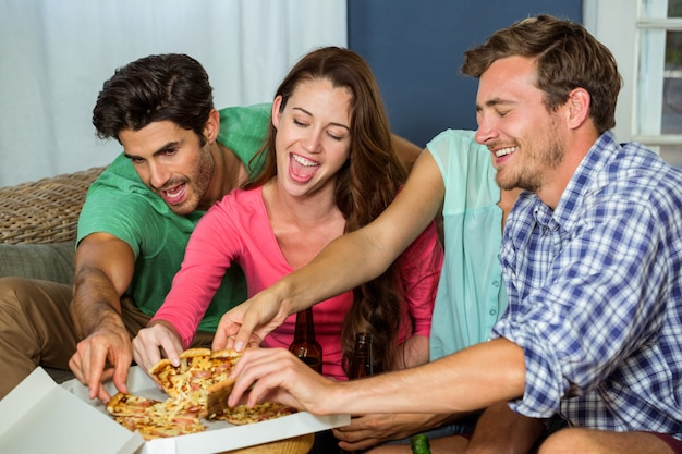 Happy friends picking up piece of pizza